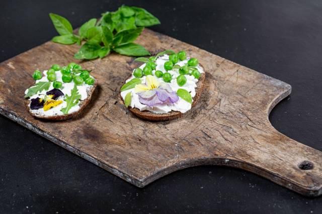 Käsesandwiches mit grünen Erbsen, Basilikumblättern und essbaren Blumen auf einem rustikalen Holzbrett