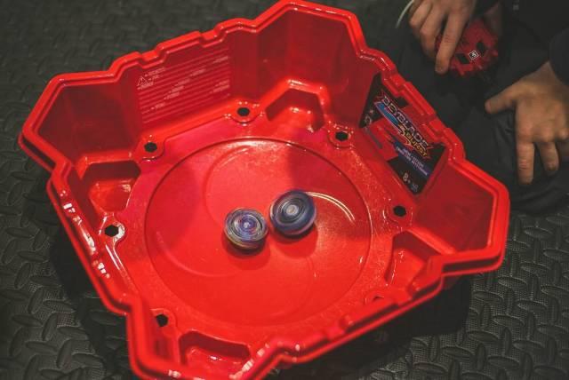 Beyblade Zirkel in roter Arena mit daneben kniendem Spieler