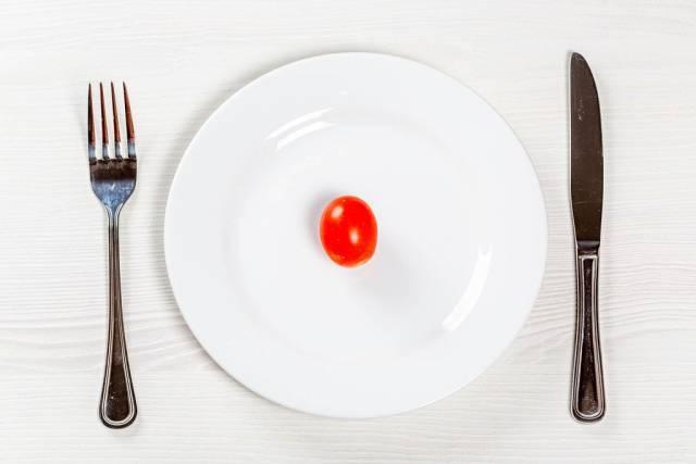 Rote kleine Tomate auf weißem Teller mit Besteck - Konzept der Ernährung