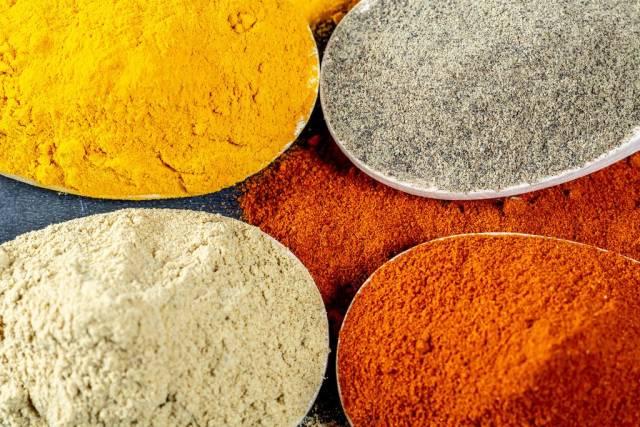 Blick von oben auf Schalen mit Gewürzen zum Kochen von aromatischen Gerichten