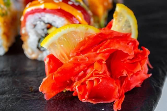 Dünne Scheiben geschnittener, eingelegter Ingwer, dekoriert mit Zitrone vor Sushirolle