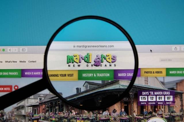 Webseite des Mardi Gras in New Orleans, Louisiana mit durch Lupe hervorgehobenem Logo