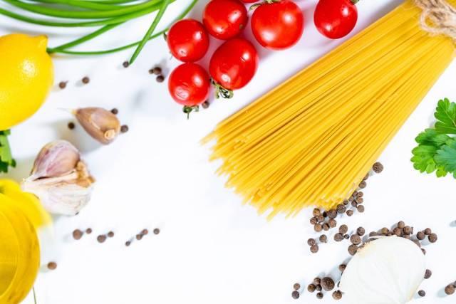 Angerichtete Zutaten für Spaghetti wie Pasta, Tomaten, Knoblauch, Pfeffer, Zitrone und Kräuter