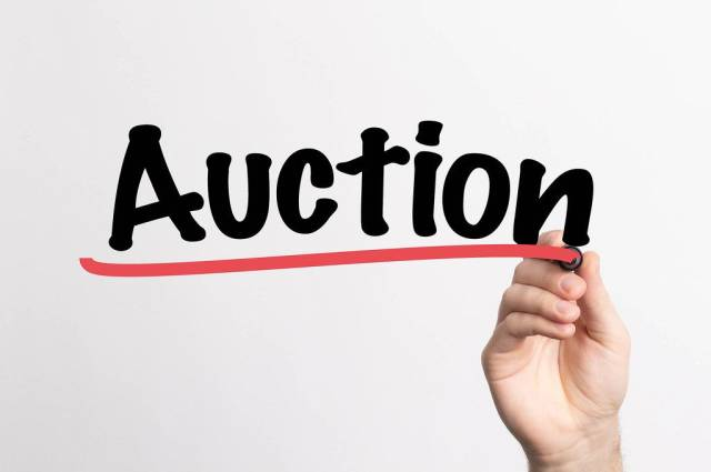 """Hand schreibt """"Auktion"""" auf ein Whiteboard"""
