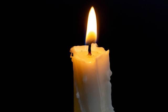 Brennende Kerze mit heller Flamme mit schwarzem Hintergrund Nahaufnahme
