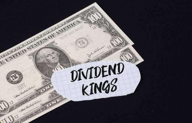 """Dividend kings"""" Text auf kariertem Zettel mit zwei 100-Dollar-Scheinen vor schwarzem Hintergrund"""