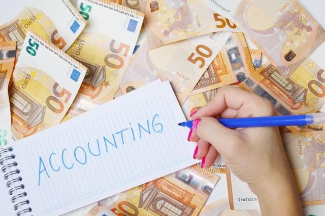 """Frau schreiben """"Accounting / Buchhaltung"""" auf einen Zettel zwischen 50-Euro-Geldscheinen"""