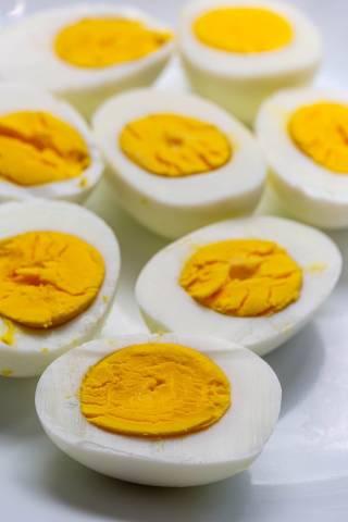 Halbierte, gekochte Eier auf einem weißen Teller