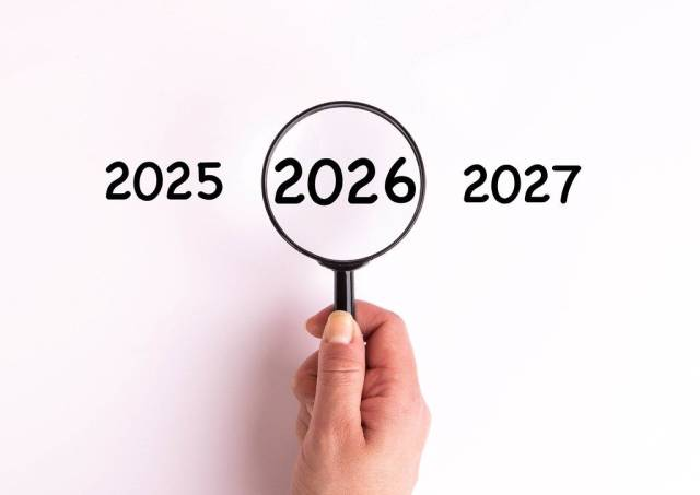 Jahreszahl 2026 auf weißer Oberfläche unter einer Lupe dargestellt