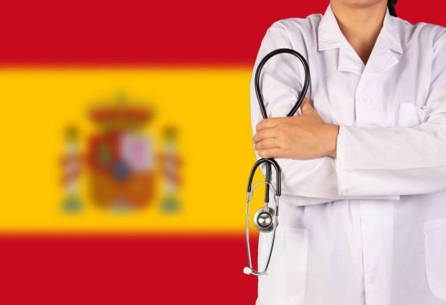 Spanische Gesundheitssystem symbolisiert durch die Nationalflagge und eine Ärztin mit Stethoskop in der Hand