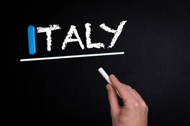 """Hand schreibt das Wort """"Italy"""" - Italien - mit Kreide auf eine schwarze Tafel"""