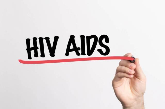 """Hand schreibt """"HIV Aids"""" auf ein Whiteboard"""