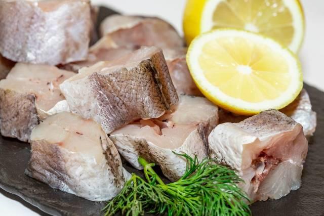 In mundgerechte Stücke geschnittener frischer roher Fisch mit Zitrone und Kräutern auf Schieferplatte