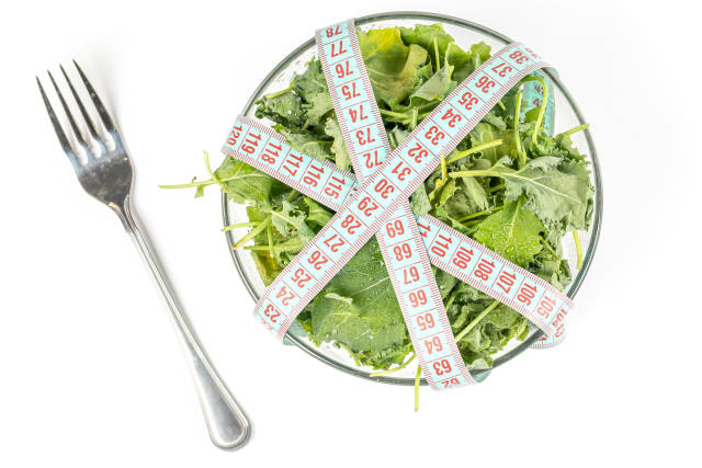 Bowl with kale leaves and measuring tape, diet food concept