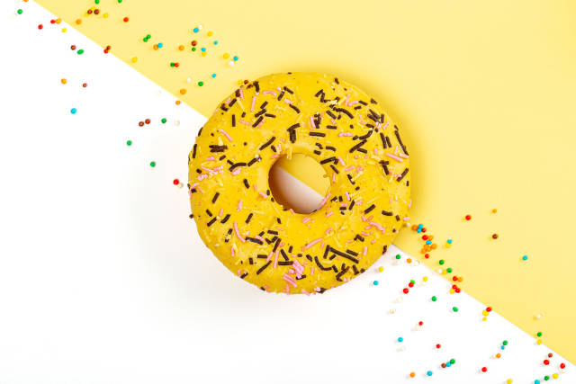Donut with sprinkles on white yellow background, top view