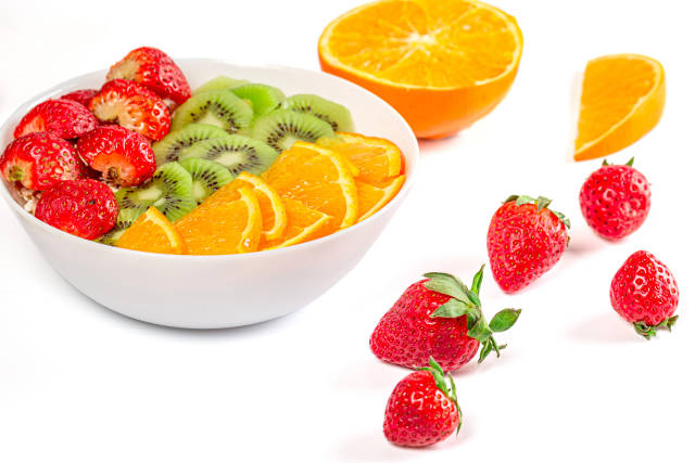 Healthy food - oatmeal with fresh strawberries, orange and kiwi