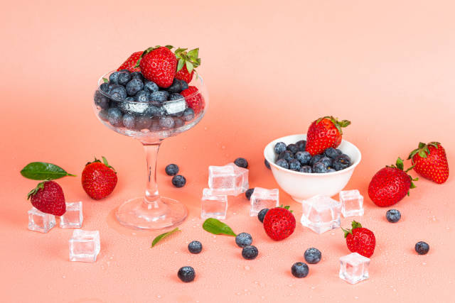 Ripe summer berries - blueberries and strawberries, ice cubes an
