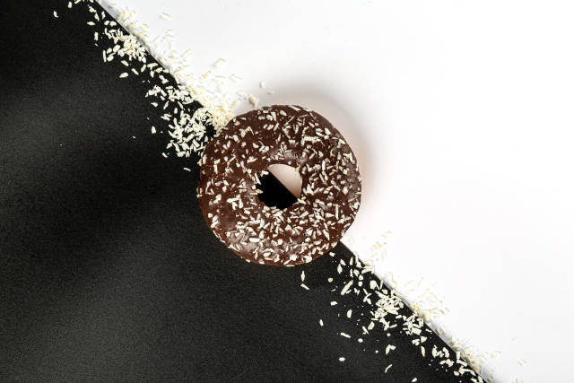 Top view, a doughnut with chocolate and coconut chips on a black