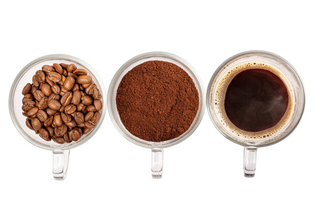Three glass cups with prepared coffee, whole grains and ground coffee on a white background, top view