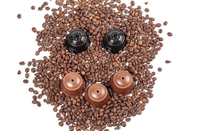 Face with a smile made from coffee beans and capsules for a coffee machine