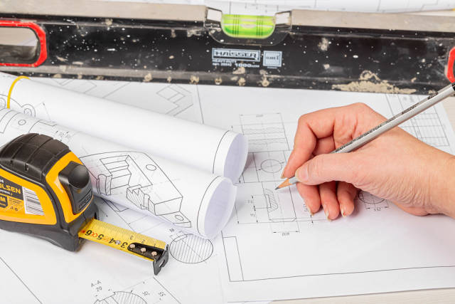 Workspace with drawings, measuring tape, level, and hand with pencil