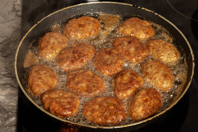 Meat cutlets are fried in a frying pan