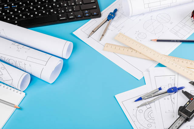 Blueprints and blueprint rolls with a drawing instruments on the worktable