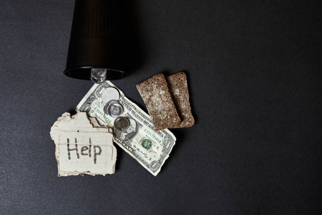 Beggar can with slices of moldy bread, coins and coins
