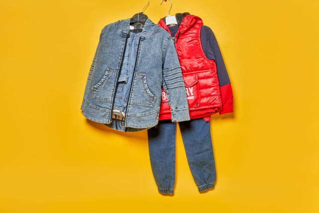 Pair of fashionable kid clothes hanged over the yellow backdrop