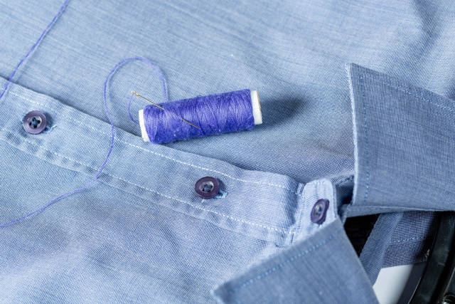 A spool of blue thread and needle on a mans shirt