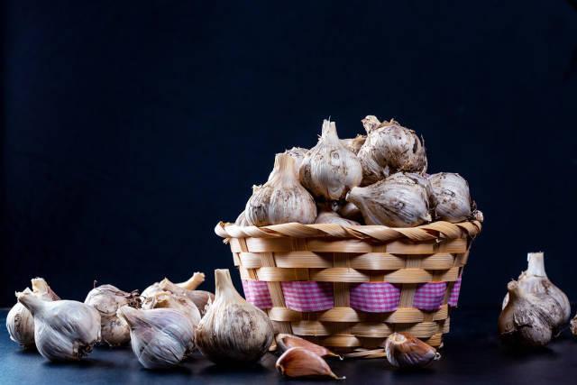 Wicker basket full of garlic on black background