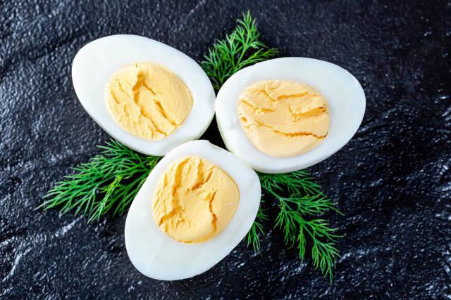 Halves of cut boiled chicken eggs on dark background