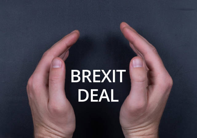 Brexit deal text with man hands on black bacground