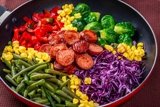 Frying pan with vegetables and sausages