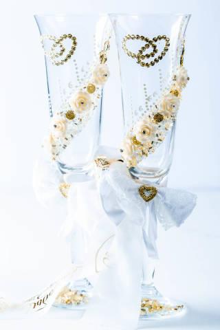 Wedding glasses and wedding decor with ribbon on white background