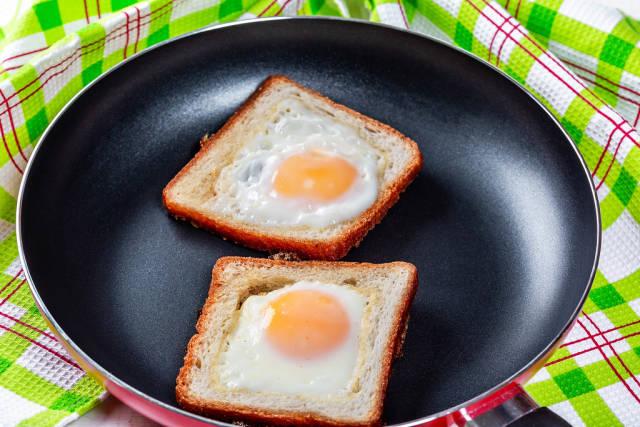 Fried eggs in toast bread in a frying pan