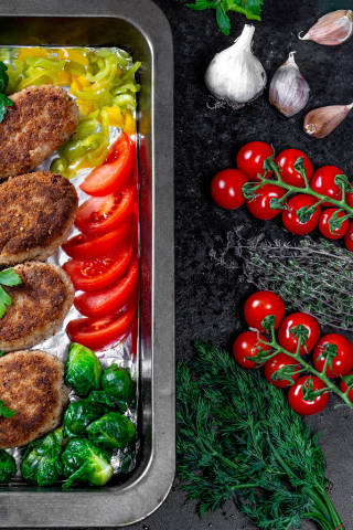 Top view of delicious fresh meat patties with vegetables and greens on black background