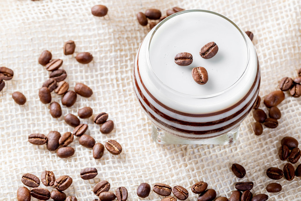 Chocolate-milk dessert with coffee beans on the background of burlap