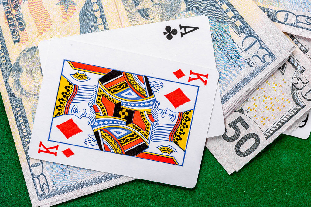 Two cards-ace and king with dollars on the green table