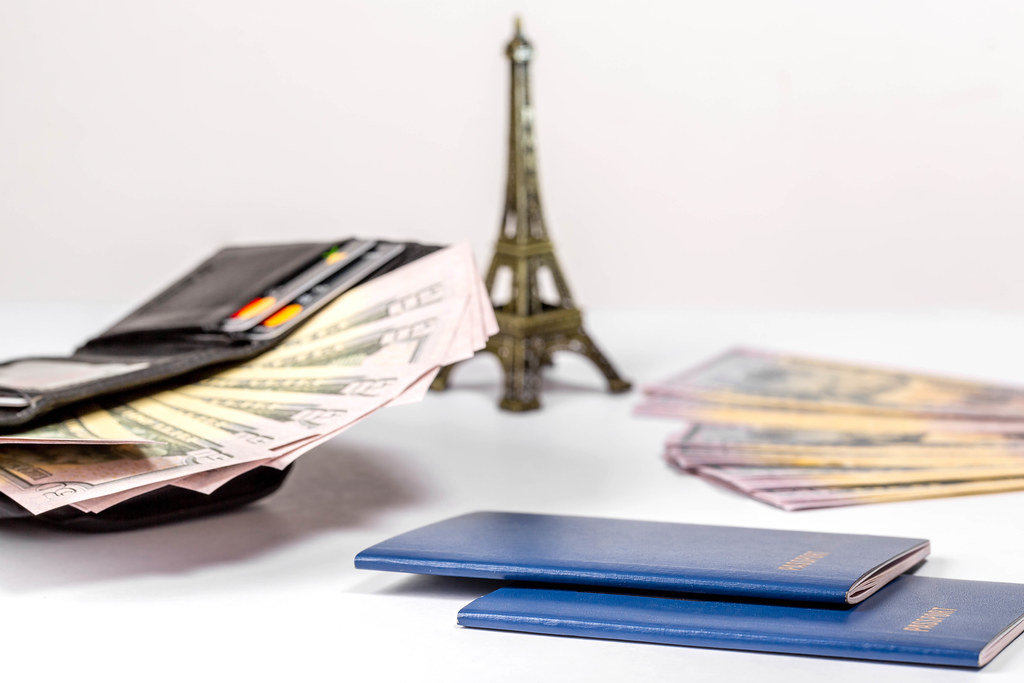 Passports, open wallet with cards and money and the Eiffel tower on white background