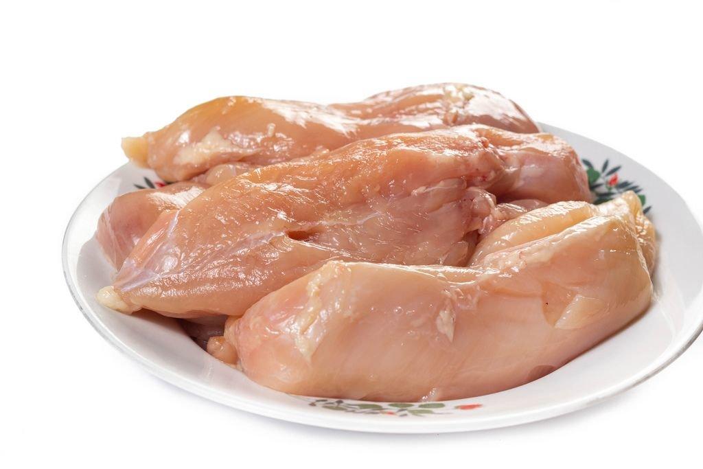Stücke rohe Hähnchenbrust auf Teller vor weißem Hintergrund