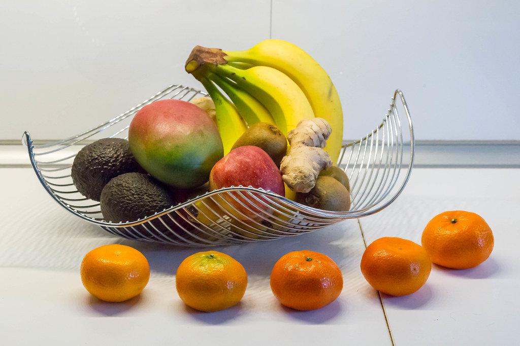 Obstkorb und Gemüse: Bananen, Avocados, Mandarinen, Mangos und Ingwer