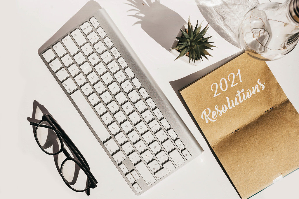 Top view of flat lay with keyboard, glasses, plant and notebook with 2021 goals. New year resolution.