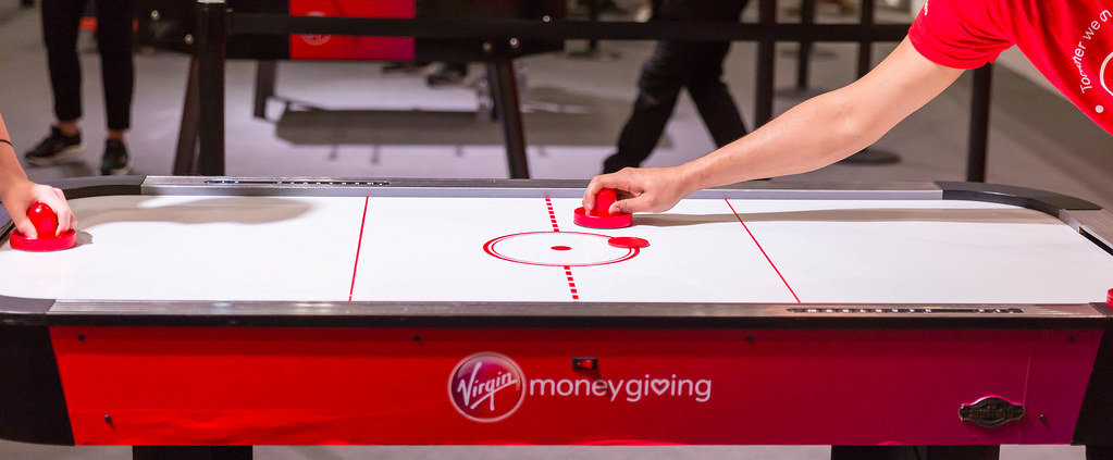 Two people playing air hockey