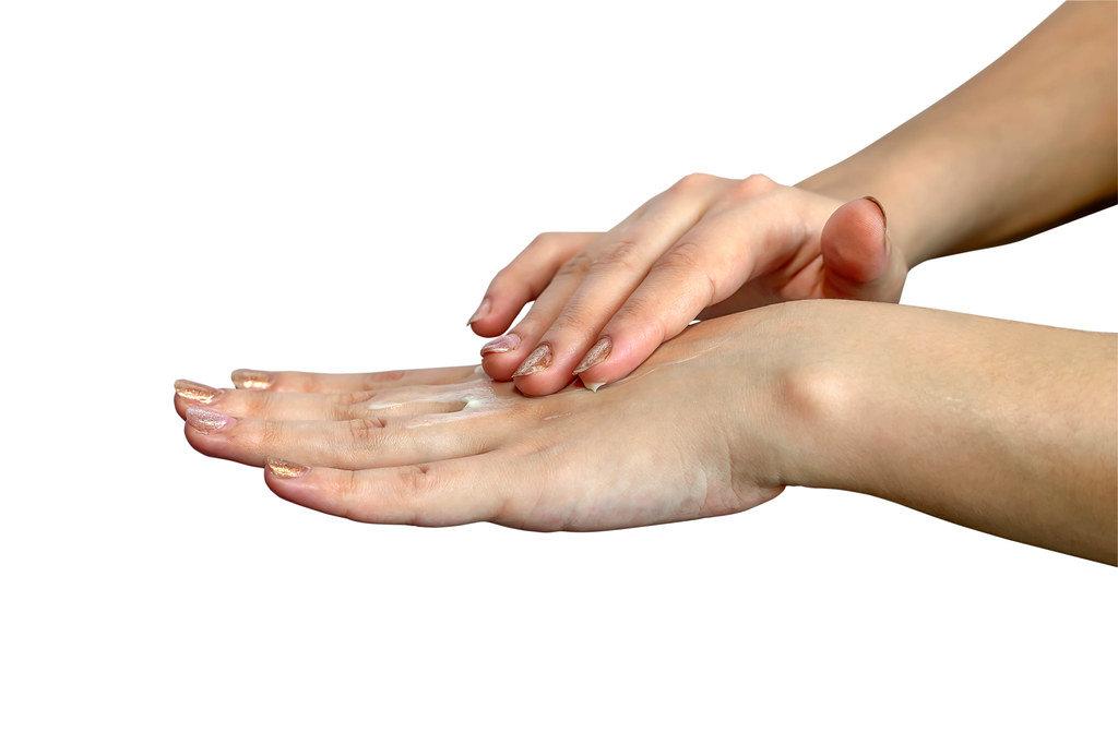 Female hands applying hand cream isolated on white