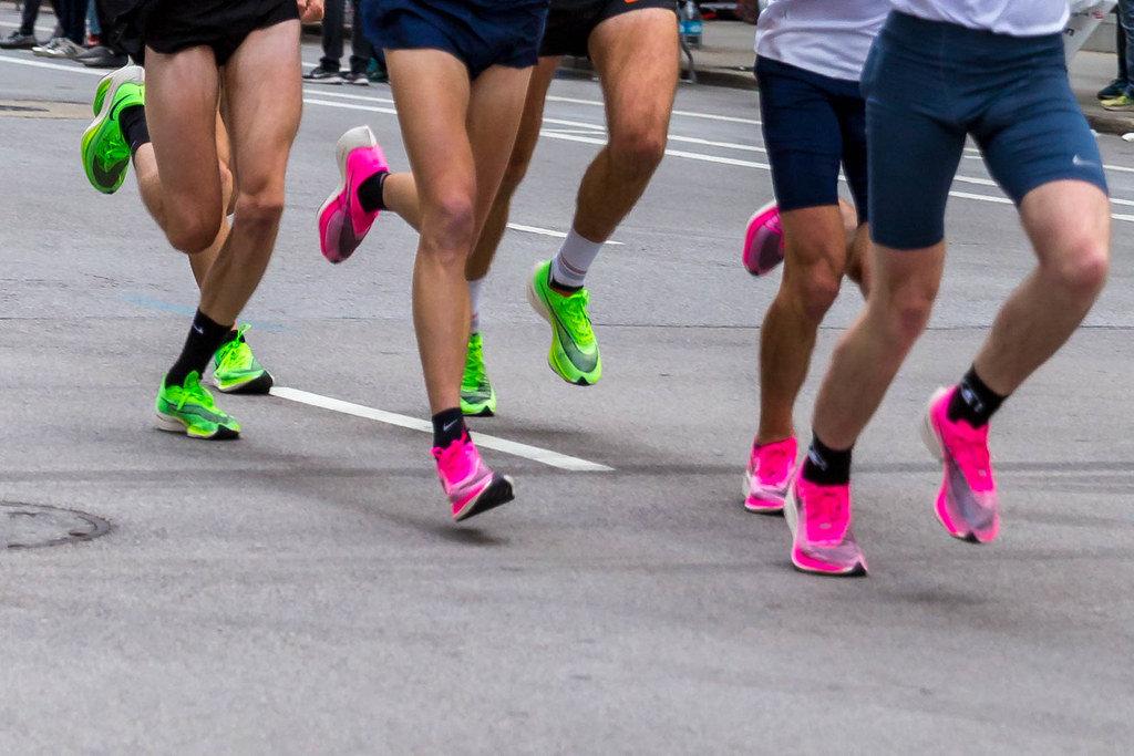 Die Beine von mehreren Marathonläufern in Nike ZoomX Vaporfly Next% Laufschuhen beim Chicago Marathon 2019