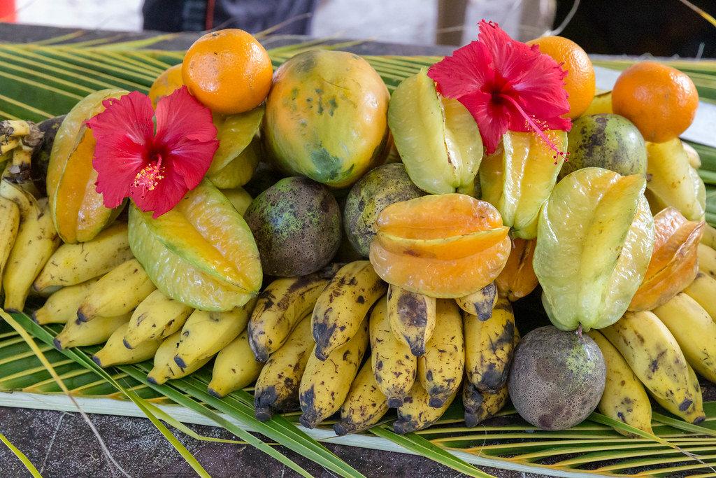 Seychellen-Obst auf Palmenblätter gestapelt, mit Bananen, Mangos, Sternfrucht und Orangen am Anse Source dArgent Strand auf La Digue