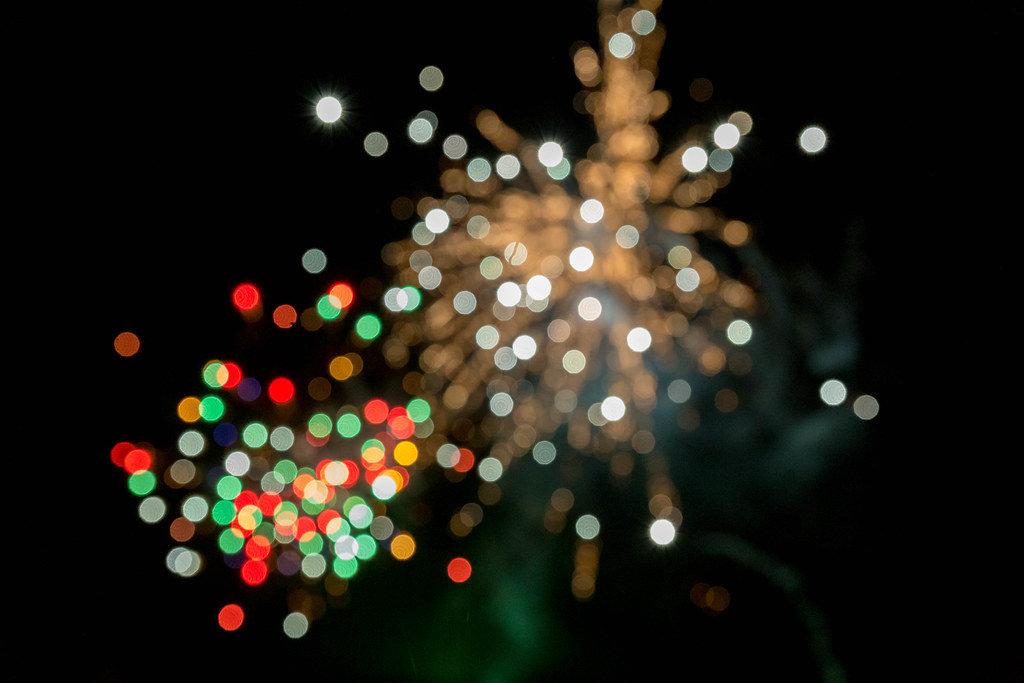 Feuerwerk zu Silvester mit weißen, roten und grünen Lichtern in Bokeh Effekt