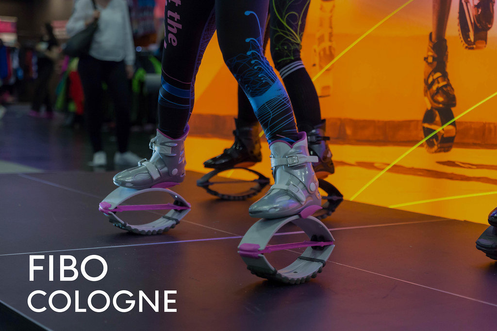"""Sports fair visitors test Kargo Jumps with futuristic looking jumping shoes for fitness training, next to the picture title """"Fibo Cologne"""