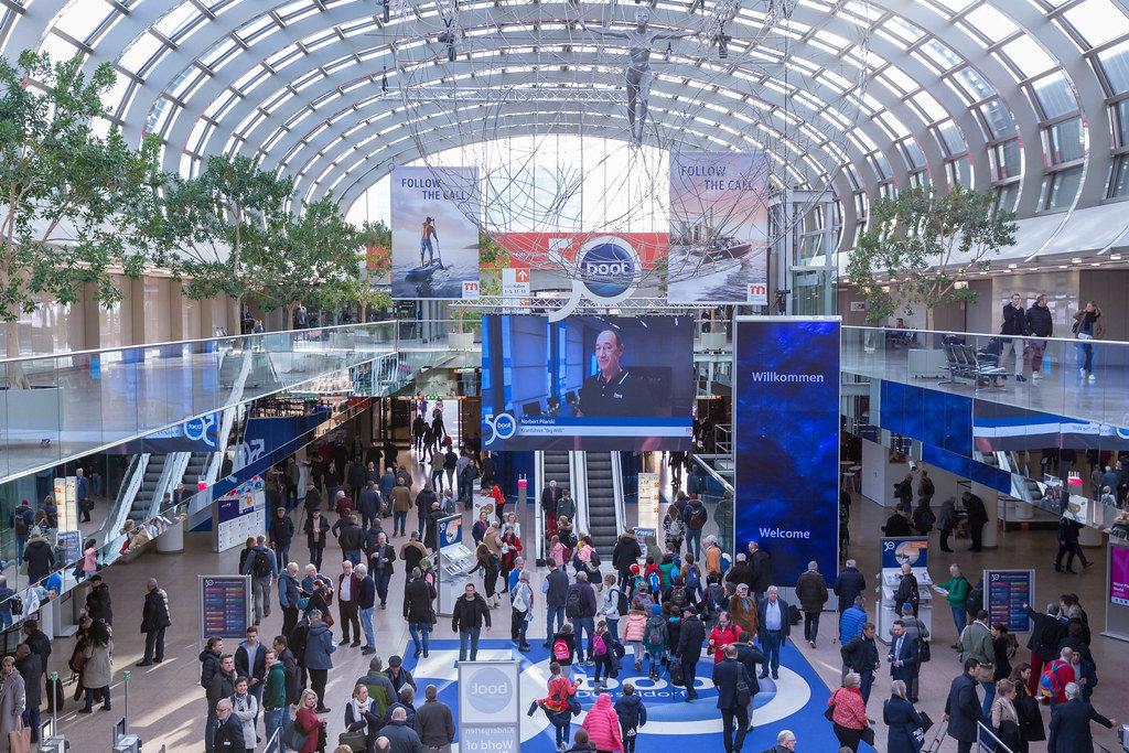Blick auf Eingangshalle der boot Düsseldorf mit Besuchern und Plakaten zum 50. Messejubiläum